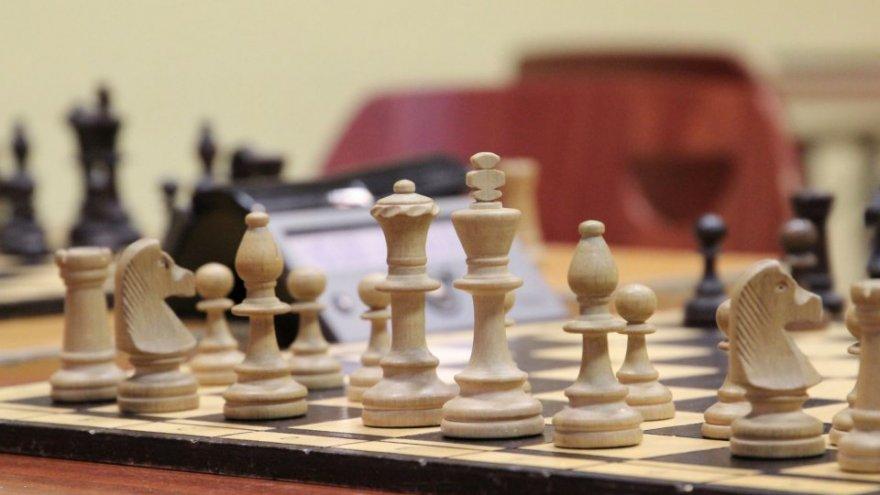 Na pierwszym planie znajduje się szachownica z ustawionymi pionkami do gry. Dalej widać zegar szachowy oraz oparcie krzesła.  Autor zdjęcia Roksana Figura.