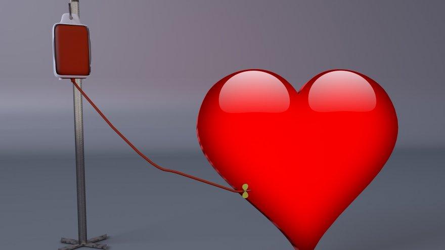 Na szaro-niebieskim tle widzimy wielkie czerwone serce, do którego podłączona jest kroplówka w kolorze czerwonym, umocowana na stojaku.   Autor zdjęcia: kalhh z Pixabay