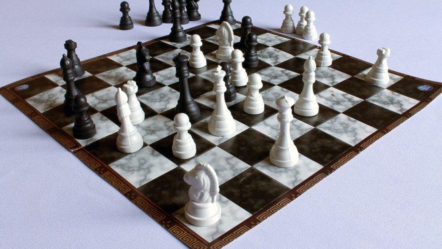 Szachownica z pionkami na białym tle. Kilka pionków poza planszą.  Obraz Adriano Gadini z Pixabay