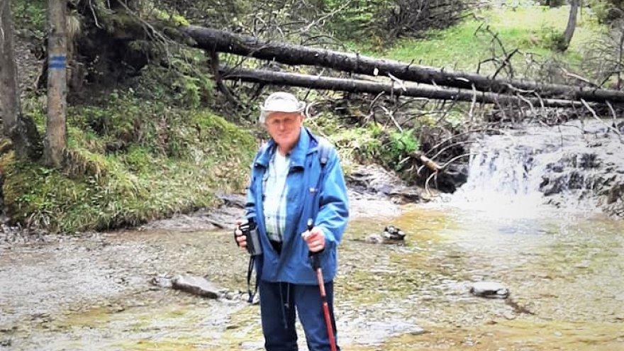 Wysoki mężczyzna w białym kapeluszu, niebieskiej, rozpiętej kurtce i dżinsach trzyma w rękach kijki trekkingowe. Stoi na brzegu rzeki. Za nim widać stojące i leżące drzewa.