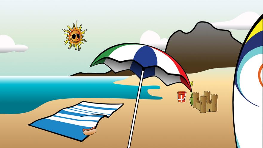 Grafika przedstawia plażę, na której znajdują się: koc, na nim hot dog, obok rozłożony parasol, wiaderko, zamek z piasku. W tle widać nadmorskie wydmy i uśmiechnięte słoneczko. Obraz OpenClipart-Vectors z Pixabay