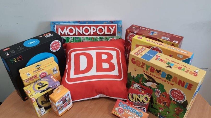 Na zdjęciu znajdują się różnorodne gry planszowe oraz poduszka z napisem: DB
