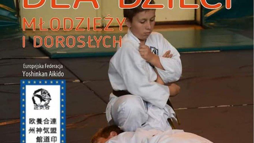 Na plakacie widzimy dwoje dzieci w wieku szkolnym, które ubrane są w kimona i ćwiczą sztuki walki na podłodze sali treningowej wyłożonej materacami. Napisy: AIKIDO DLA DZIECI MŁODZIEŻY I DOROSŁYCH. Europejska Federacja Yoshinkan Aikido.