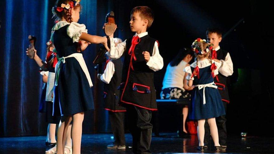 Na zdjęciu widać tańczące na scenie dzieci w strojach ludowych.